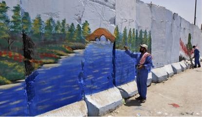 Homem faz uma pintura no muro que protege a parte sul do enclave xiita da Sadr City, em Bagdá. (Karim Kadim/Associated Press)
