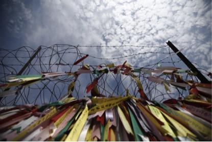 Foto de outubro de 2014, cerca de arame farpado com fitas coloridas com mensagens pro unificação das 2 Coreias. (Kim Hong-Ji/Reuters).
