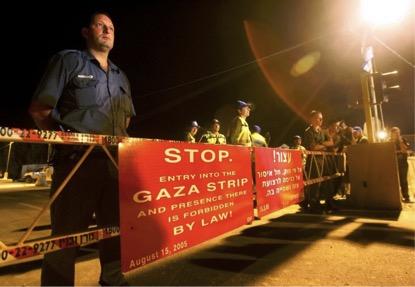 Faixas em inglês e hebraico bloqueiam estrada que leva a Gaza. Guardas israelenses protegem os 64 quilômetros da fronteira com a faixa de Gaza, erigida em 1994. (Getty Images/David Silverman)