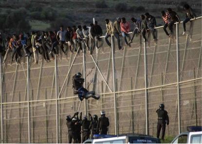 Foto de outubro de 2014 mostra um guarda civil espanhol puxando um imigrante africano tentando atravessar a fronteira entre Melilla (cidade autônoma espanhola, situada no norte de África) e o Marrocos. (Jesus Blasco de Avellaneda/Reuters)